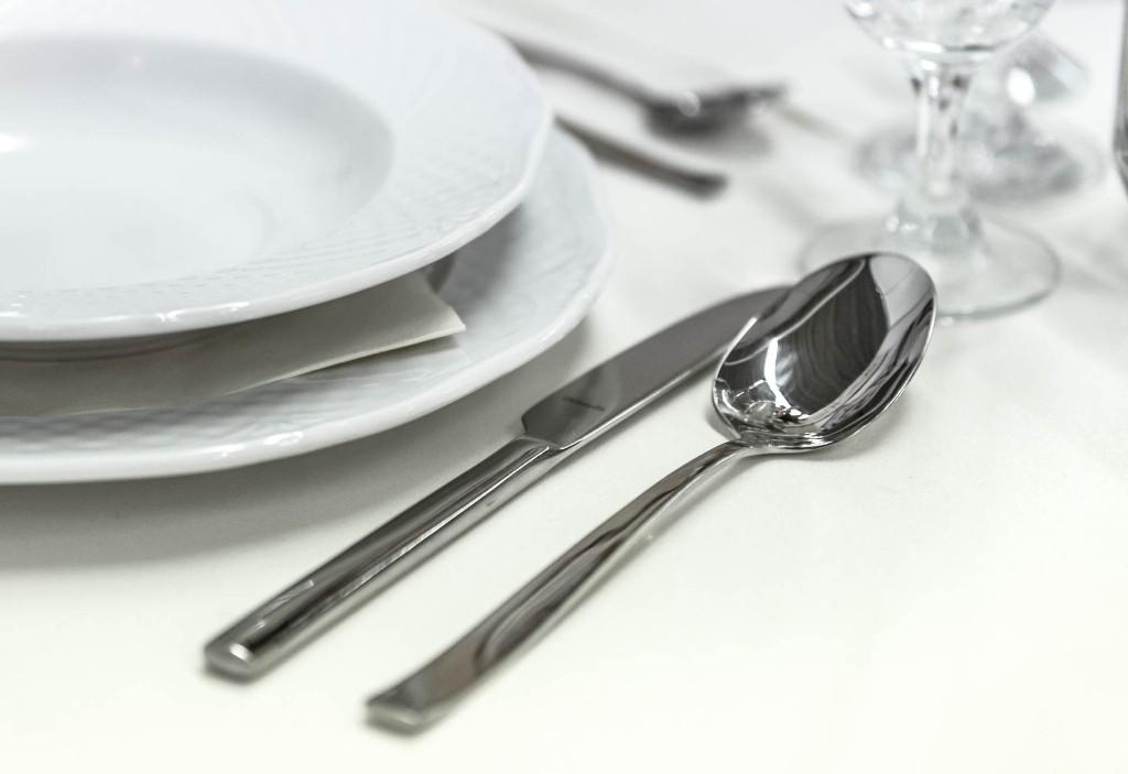 Messer und Löffel neben Teller